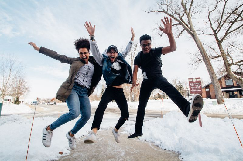 A group of three friends jumping together in the snow.