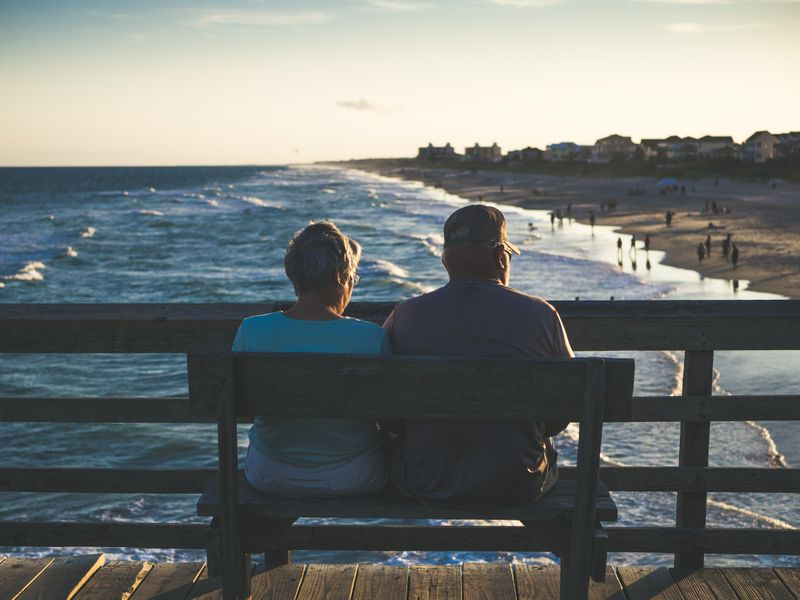 Older woman and older man sitting on a bench on a boardwalk overlooking the ocean.