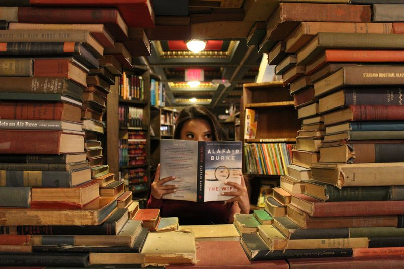 Woman reading book surrounded by stacks of books.