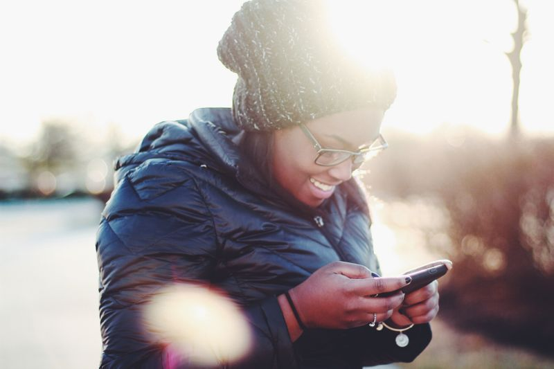 a women smiling at her phone while texting