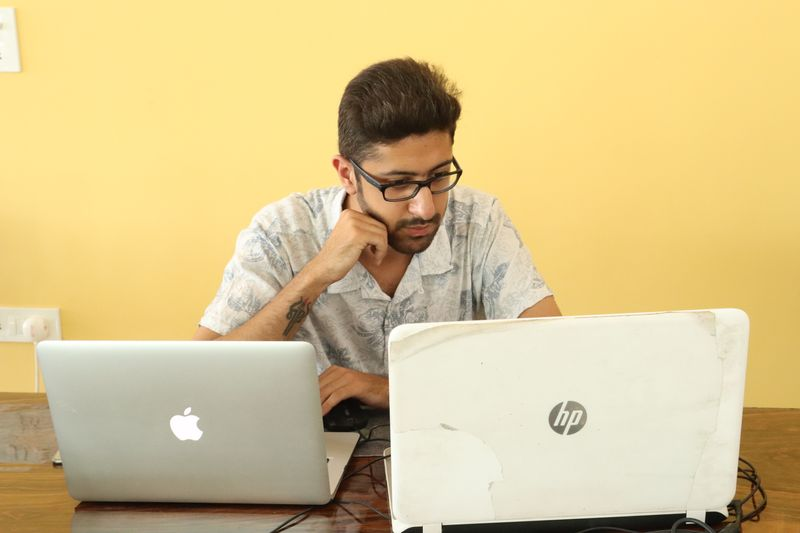 A person looking at two laptops