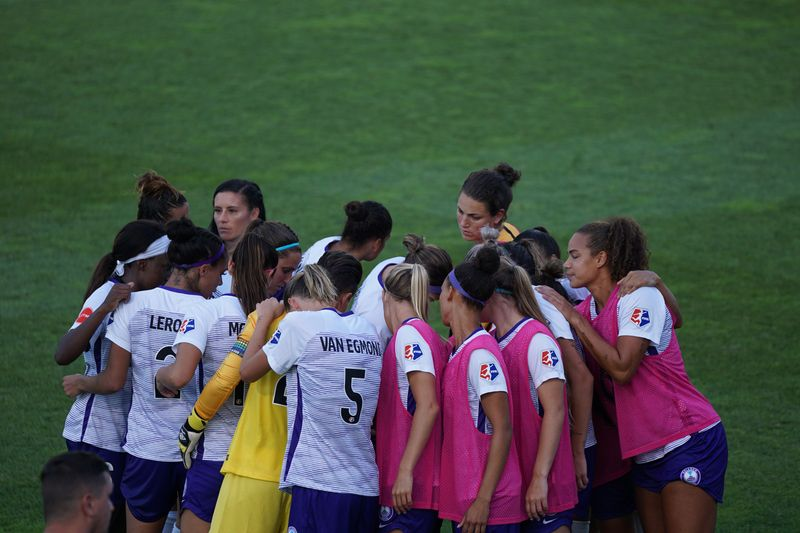Women's football team in a huddle.
