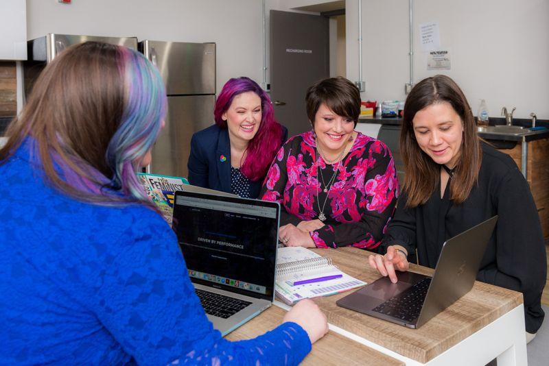 Four women in an office working on laptops