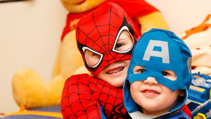 Two young kids dressed in superhero costumes as Spiderman and Captain America