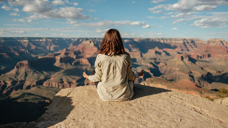 Girl meditating on a rock looking over a valley of red rock formations