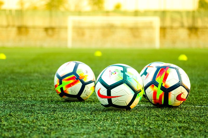 Three footballs on a training pitch practice session.