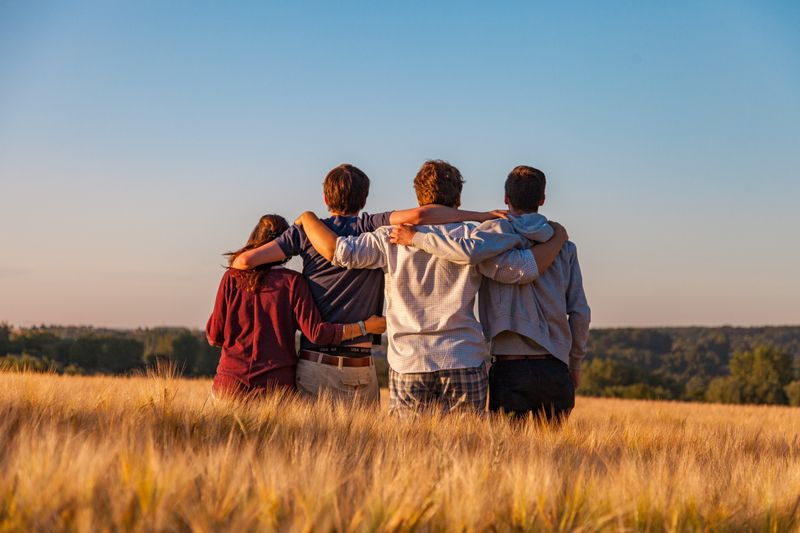 A family standing in a field with their arms on each other's shoulders comforting one another.