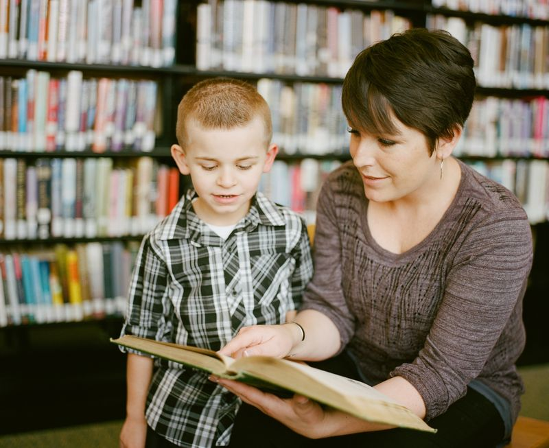 A woman reading to a child in a library