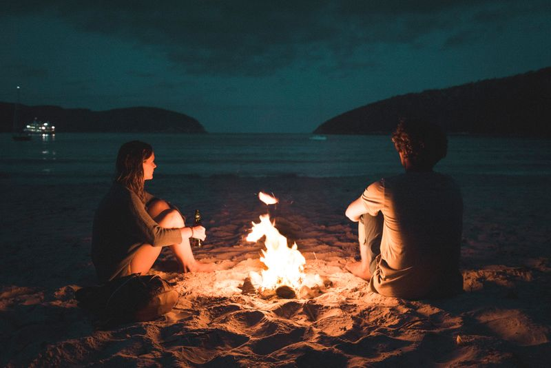 Two people on a beach in front of a camp fire