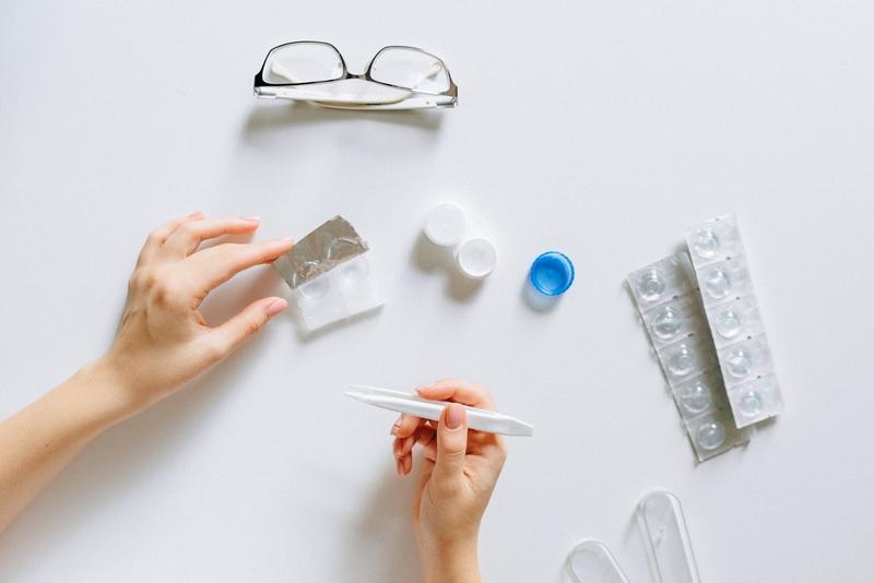 A person preparing contact lenses