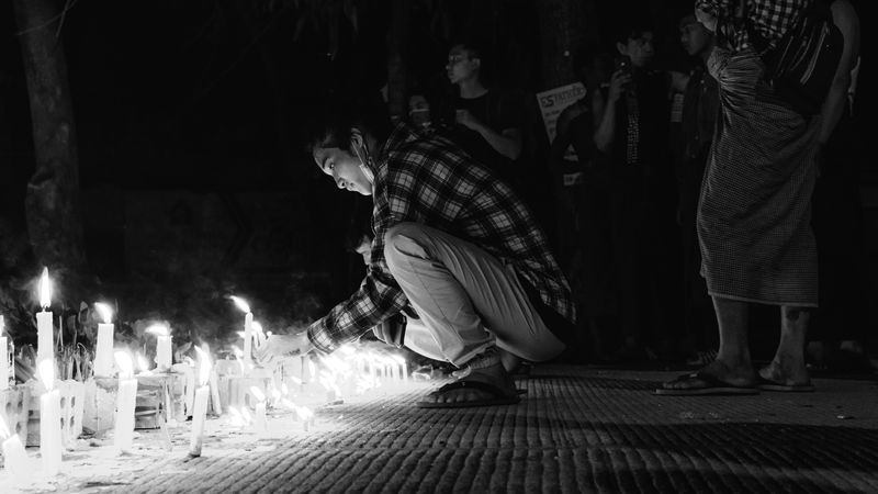 A person lighting a candle at a vigil