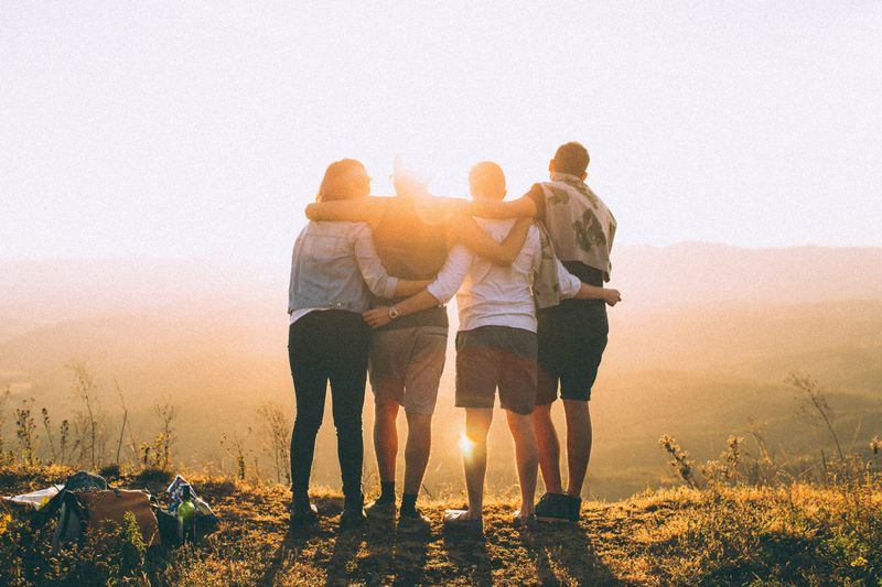 Four people looking at the sunrise with their arms around each other.