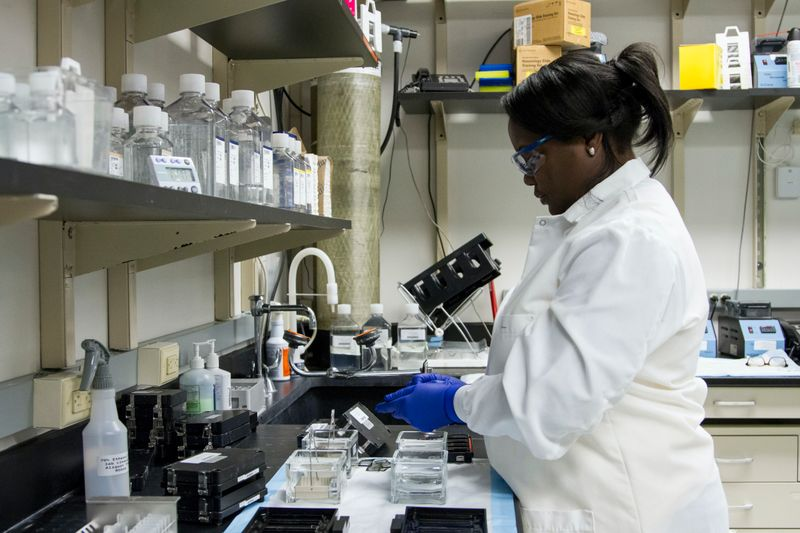 an epidemiologist wearing gloves and safety glasses works in a lab setting