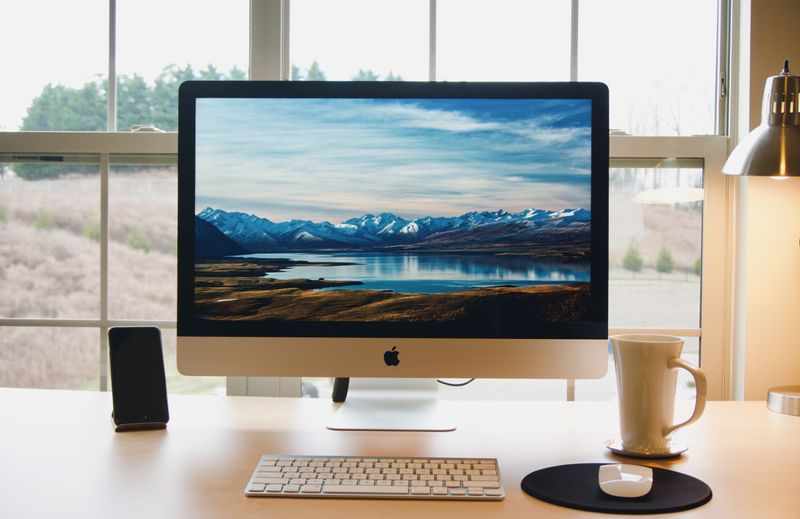 A Mac monitor on a desk showing a mountain background
