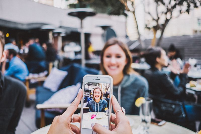 A person taking picture on iphone of a woman.