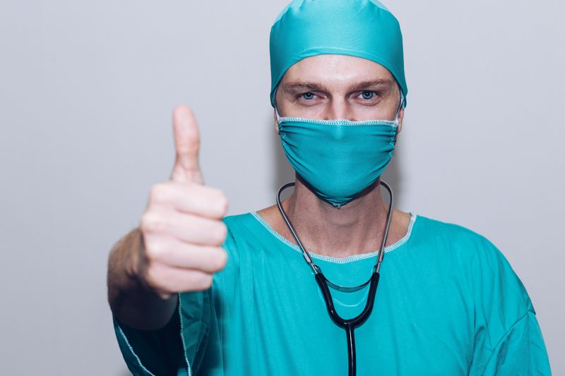 A doctor in full scrubs giving a thumbs up