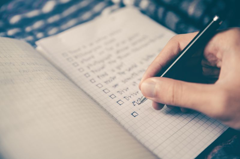 A hand writing a checklist in a notebook
