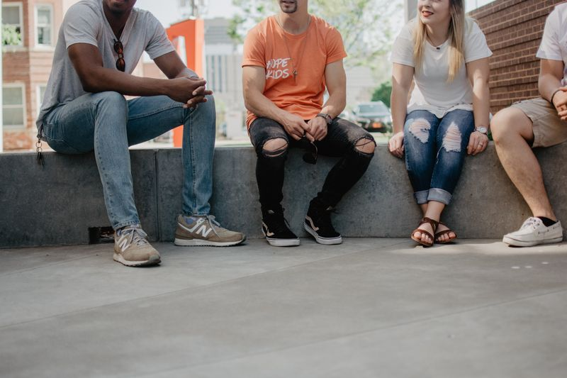 A group of four people sitting together and talking on a concrete ledge