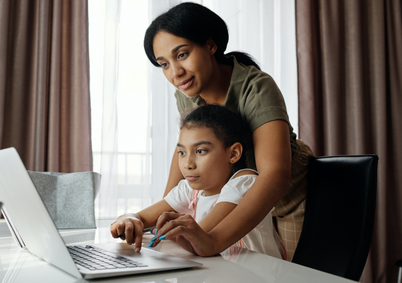 Mom helping child research on computer