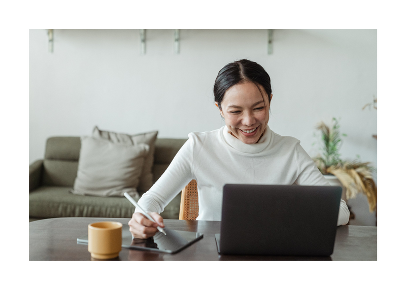 Smiling woman at a home desk writing on notepad looking at a laptop