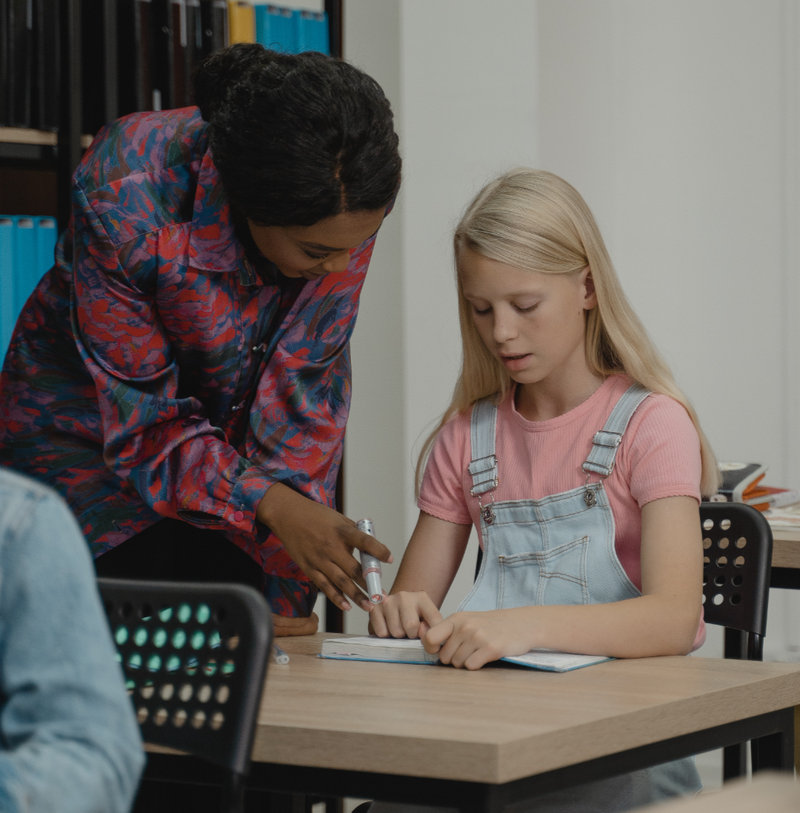 Photo of teacher helping student sitting at desk