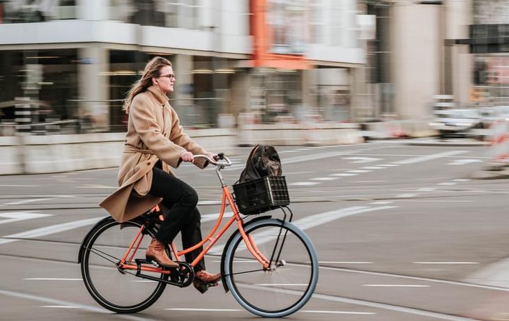 A woman riding a cruiser bike across a city street