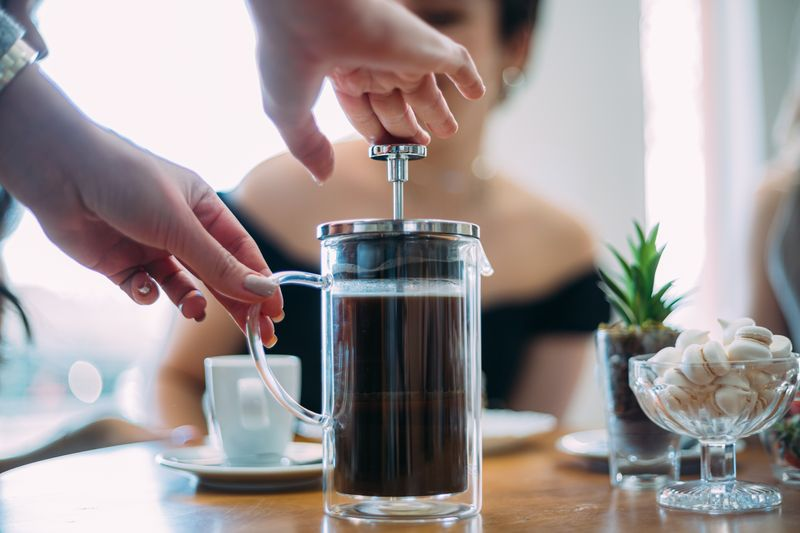 A person pressing down a pot of coffee with a french press