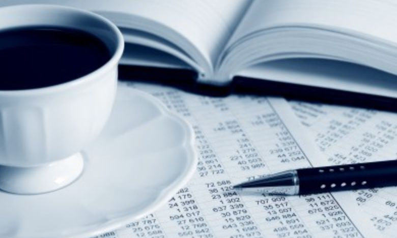 A cup of coffee on a table beside budget sheets
