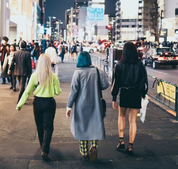 Three friends walking down a busy street at night