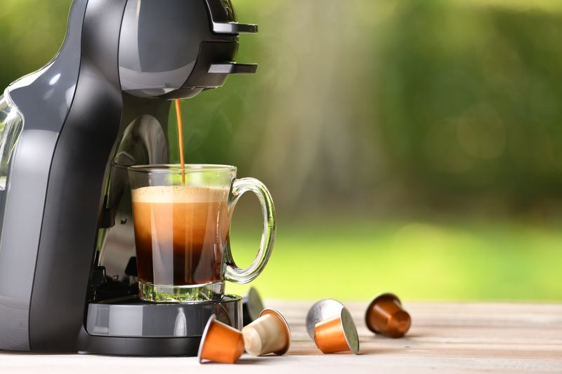 A single serve coffee machine with coffee capsules on a table