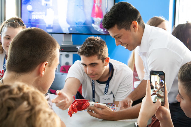 A limbitless intern demonstrating the EMG technology to student visitors