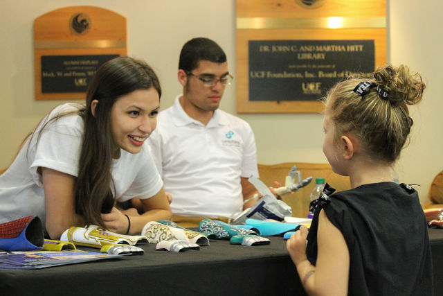 Two limbitless interns talking to a young girl while tabling at an event
