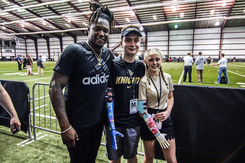 Bionic kids Anni and Wyattt posing with UCF football star Shaquem Griffin