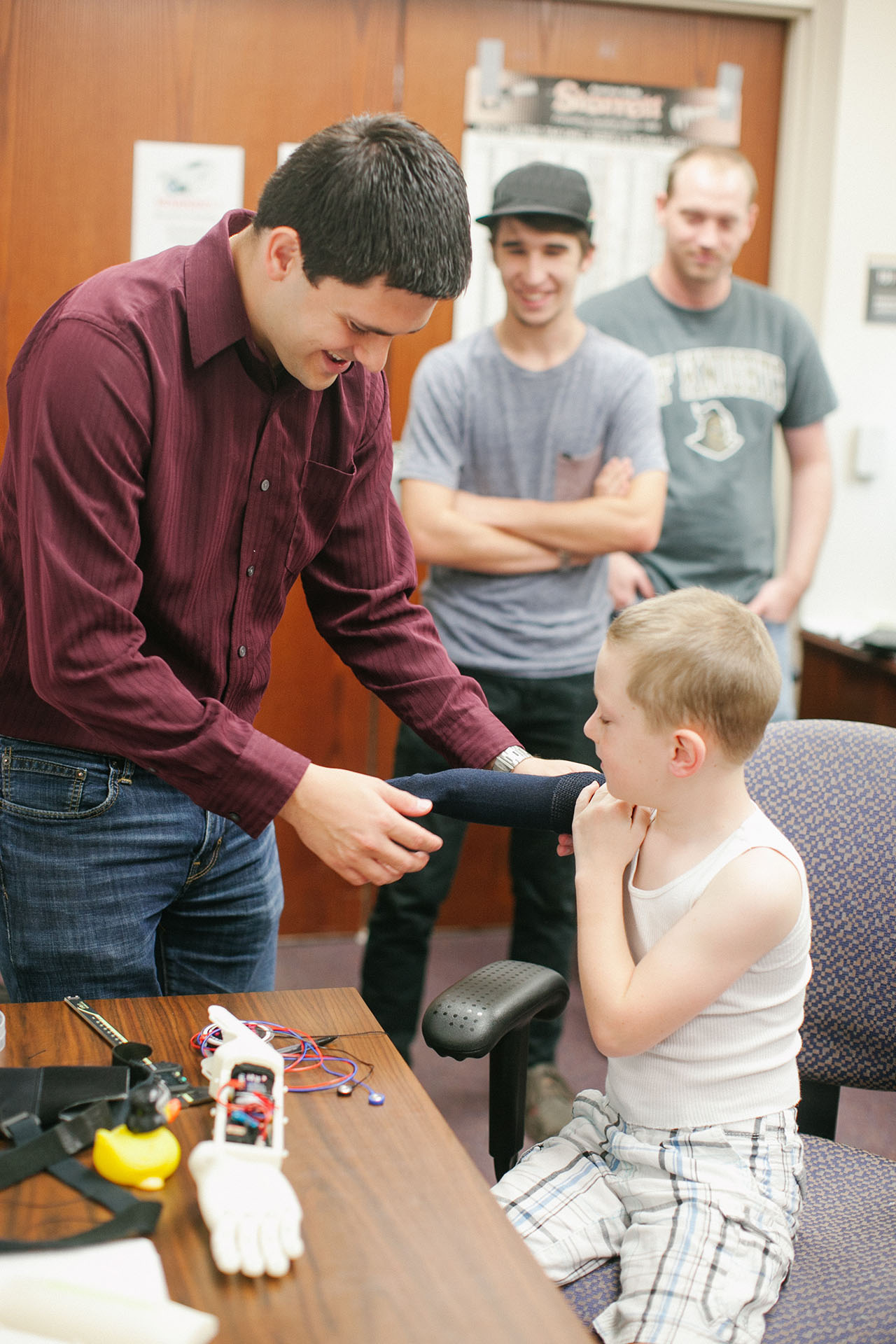 Limbitless president Albert testing the fit of Alex's bionic arm