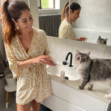 Leigh Campbell with her cat and skincare products