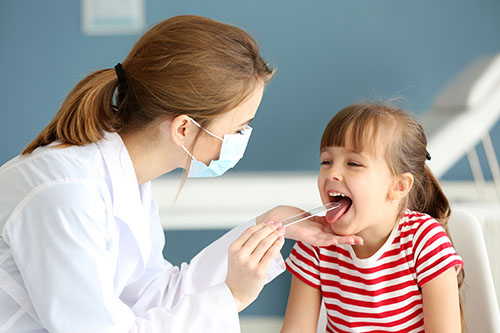 Image showing an ENT specialist diagnosing sore throat in kid
