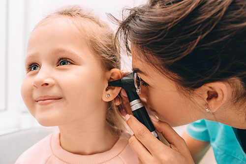 A kid being diagnosed by an ENT specialist for Otitis media