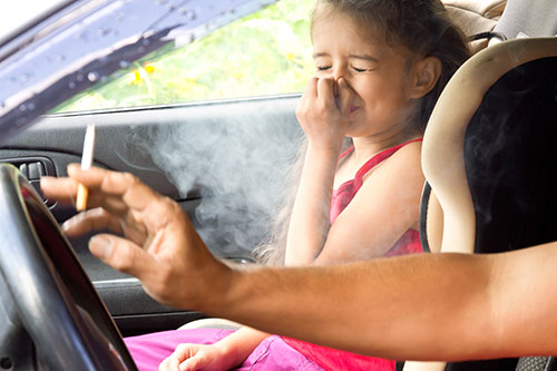 A kid getting exposed to cigarette smoke in a car