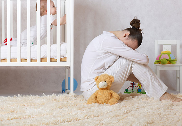 sad young mom with baby next to her in the crib