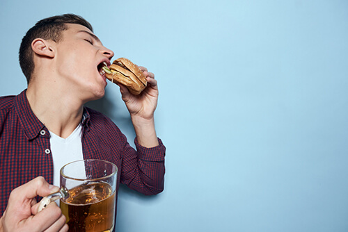 pictorial representation of a boy eating and drinking the worst things which cause colon cancer