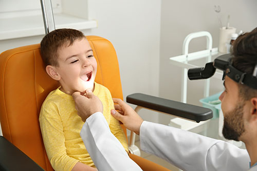 The image is showing an ENT specialist is diagnosing a kid with tonsils