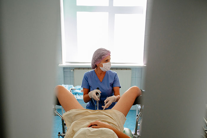Gynecologist performing Hysteroscopy on a female