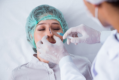 an image showing a patient under the procedure of a nose job