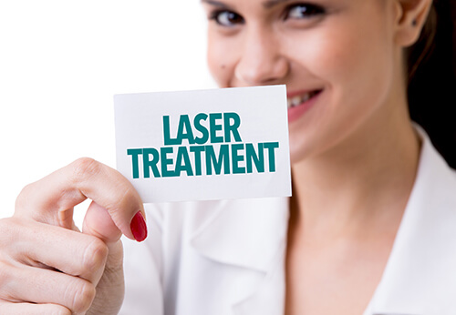 "gynecologist holding a white card with ""laser treatment"" written on it"