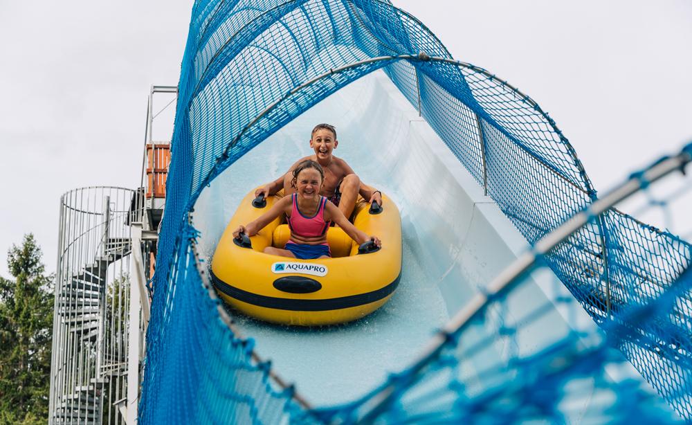Jente og gutt sitter i gummibåt nedover en vannsklie