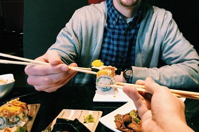 Mann holder en maki med spisepinner