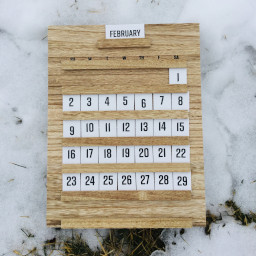 A wooden calendar laying on the snow