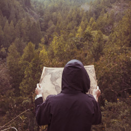 A person in the forest holding an old map