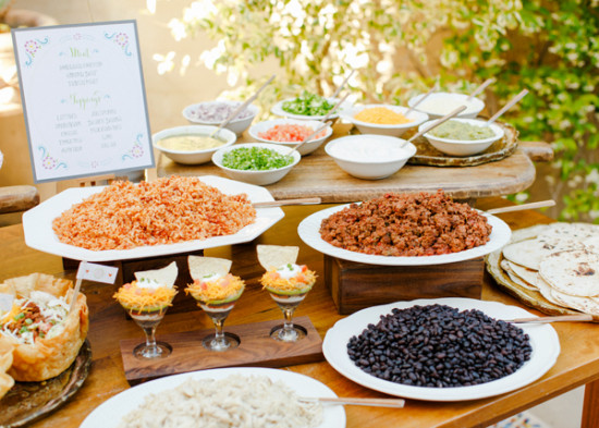 Self-serving taco bar with different ingredients laid out at party