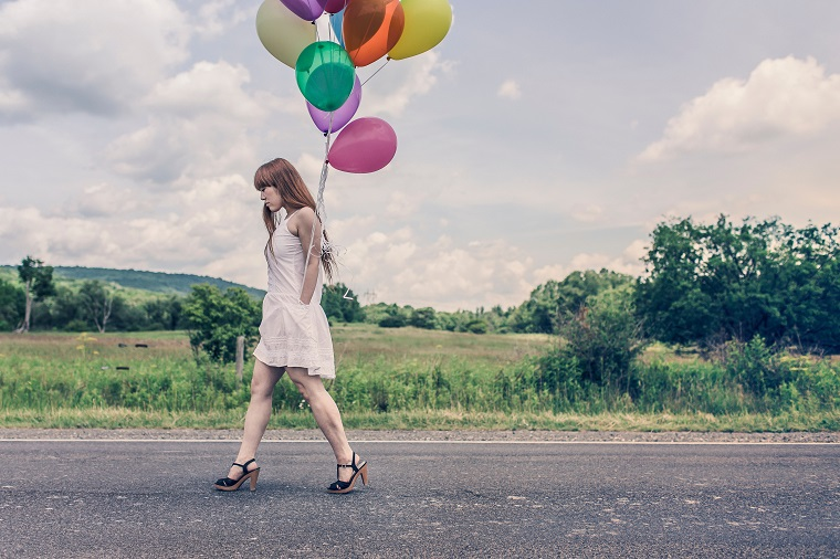 teen girl walking down the street holding balloons